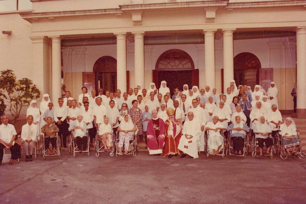 A photo taken with the Bishop, residents and the Sisters in front of the Chapel